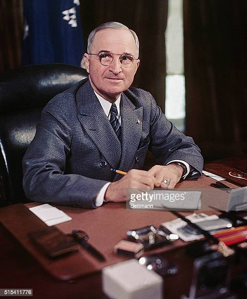 President Harry S Truman seated at his desk holding a pencil