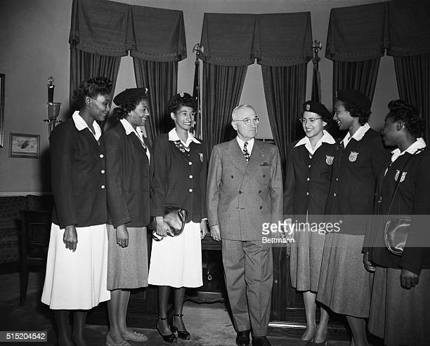 President Harry S Truman stands with a group of African American Olympic athletes in the Oval Office for the annual football game between Tennessee...