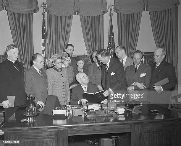 President Harry Truman receives a report from his Special Committee on Civil Rights The report handed to the President by committee chairman Charles...
