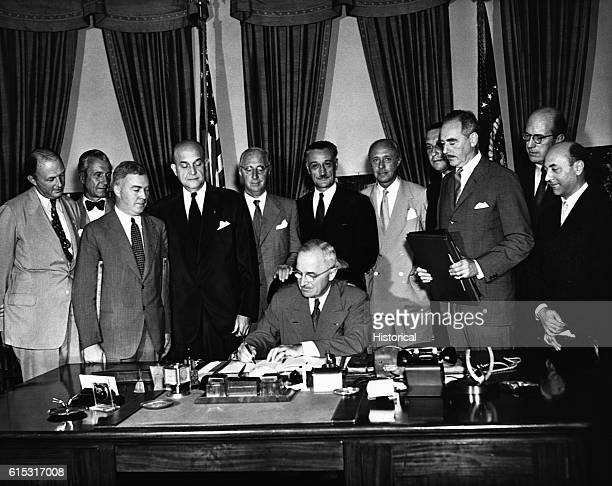 President Harry Truman signs the North Atlantic Pact creating the North Atlantic Treaty Organization as several foreign diplomats watch August 24 1949