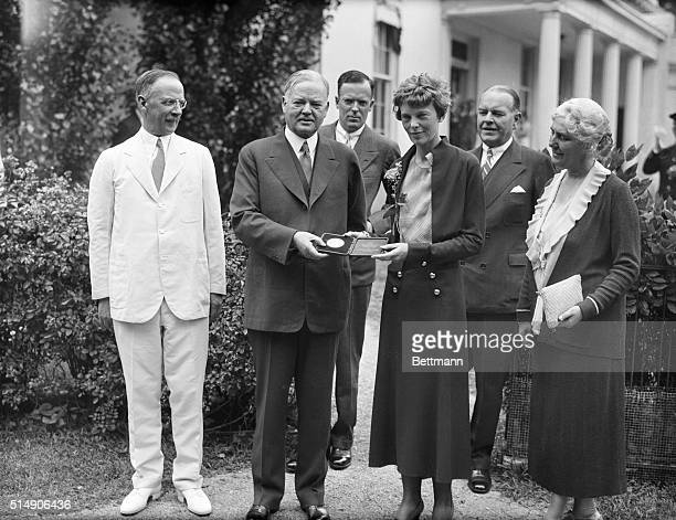 President Herbert Hoover presenting the National Geographic Society gold medal to Amelia Earhart in recognition of her continuous solo flight across...