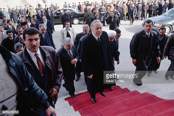 President Heydar and Azerbaijani officials walk up steps while a crowd of onlookers watch