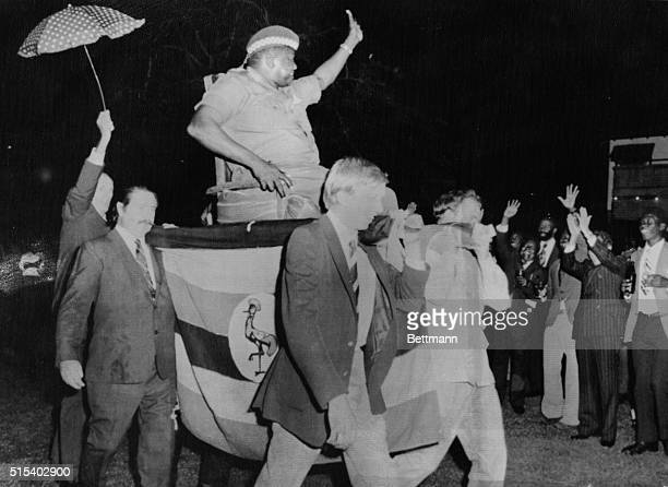 President Idi Amin is carried by four Britons into official reception here 7/18 on a makeshift throne. It was Amin's idea, to show new white mans...