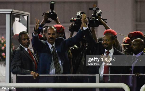 President Isaias Afwerki of Eritrea and Prime Minister Abiy Ahmed of Ethiopia salute the people gathered at the millennium hole to hear speech from...