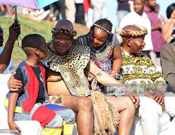 President Jacob Zuma talks to his children Snqumo and Tandesile at the wedding of his eldest son Edward on October 8 2011 in Nkandla South Africa