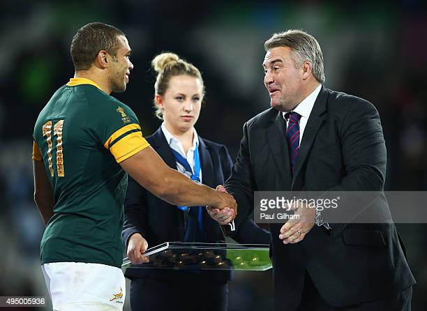 RFU president Jason Leonard shakes hands with Bryan Habana of South Africa as he is presented with his bronze medal after the 2015 Rugby World Cup...