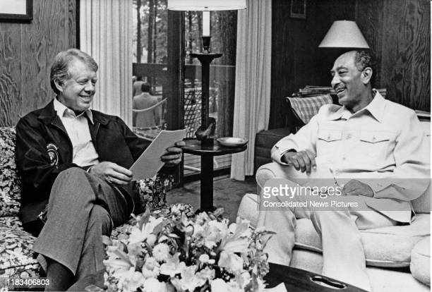 US President Jimmy Carter and Egyptian President Anwar Al Sadat share a laugh as the former reads a document during the EgyptianIsraeli peace...