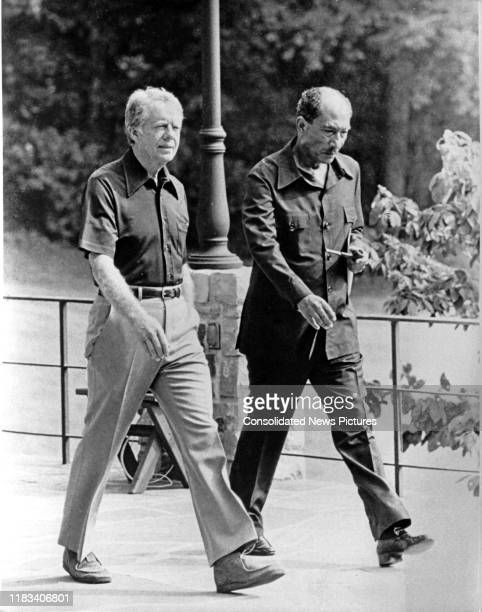US President Jimmy Carter and Egyptian President Anwar Al Sadat walk together during the EgyptianIsraeli peace negotiations behind Aspen Lodge at...