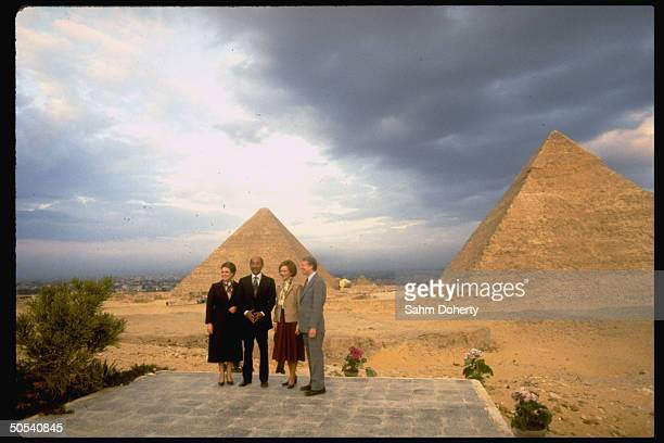 President Jimmy Carter and wife Rosalynn, Egyptian President Anwar Sadat and wife posing in front of two pyriamids in the desert.