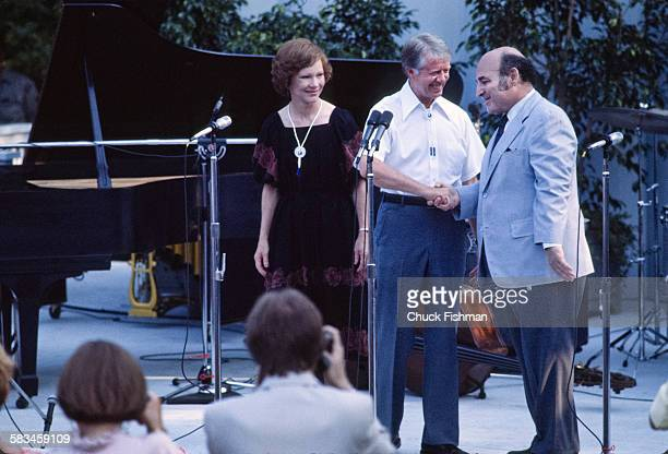 President Jimmy Carter center shakes hands with jazz festival producer George Wein at a White House Jazz Concert on the south lawn on the occasion of...