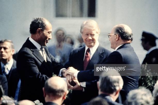 US President Jimmy Carter congratulates Egyptian President Anwar alSadat and Israeli Premier Menachem Begin in threeway handshake on March 26 1979 on...