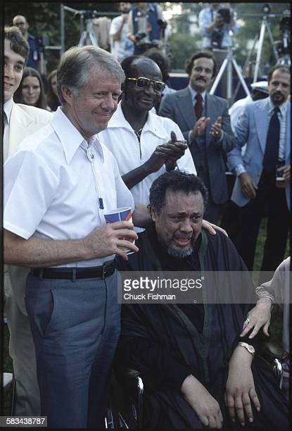 President Jimmy Carter left with a crying Charles Mingus seated in a wheelchair at the White House Jazz Concert on the South Lawn Washington DC June...