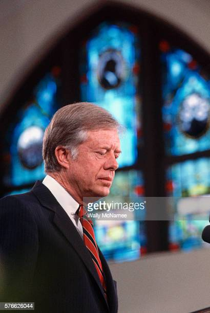 President Jimmy Carter looks solemn during a speech to the congregation of a church