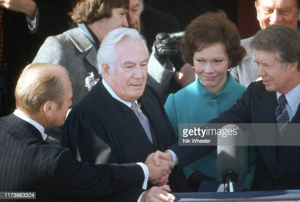 President Jimmy Carter shakes hands with ex-President Gerald Ford after he takes the oath of office from Chief Justice of the Supreme Court Warren...