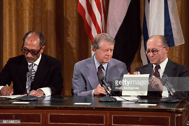 President Jimmy Carter sits between Egyptian President Anwar Sadat and Israeli Prime Minister Menachem Begin at the signing of the preliminary Camp...