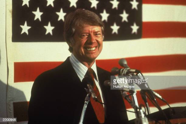 US president Jimmy Carter smiling at a podium in front of an American flag 1970s