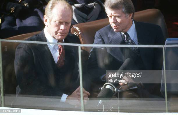 President Jimmy Carter talks to grim faced ex President Gerald Ford before he is sworn in as the new US President at Capitol ceremony January 1977;
