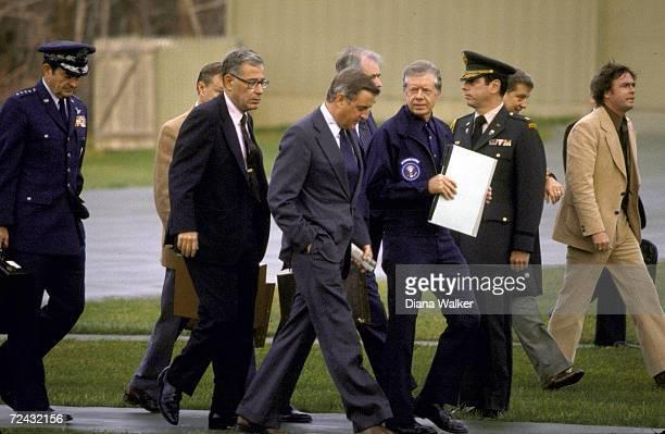 President Jimmy Carter walking with Walker Mondale Harold Brown Cyrus Vance Zbigniew Brzezinski General David Jones during meeting at Camp David on...
