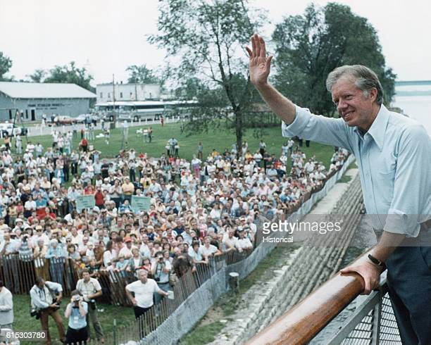 President Jimmy Carter waves to a crowd on shore from the Delta Queen on the Mississippi River August 19 1979