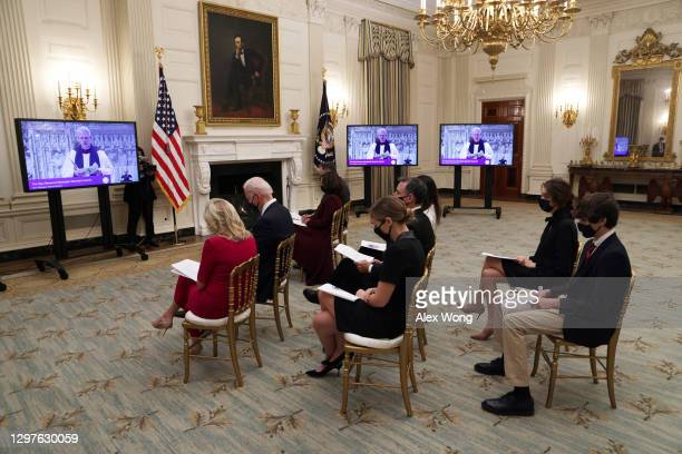 President Joe Biden and first lady Dr. Jill Biden bow their heads as they watch the virtual presidential inaugural prayer service in the State Dining...