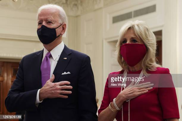 President Joe Biden and first lady Dr. Jill Biden listen to the national anthem as they watch the virtual presidential inaugural prayer service in...