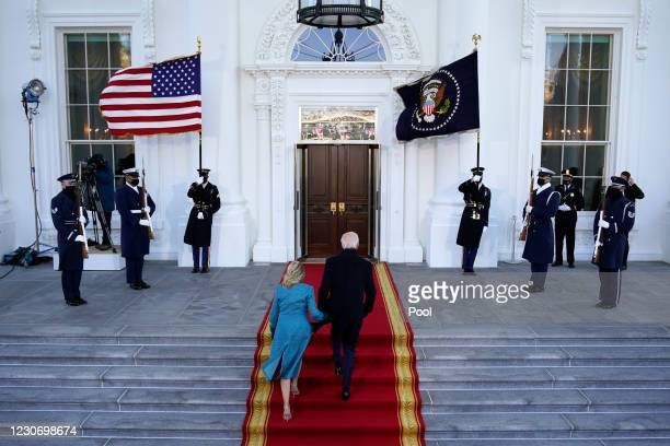 President Joe Biden and first lady Dr. Jill Biden walk up the stairs as they arrive at the North Portico of the White House, on January 20 in...