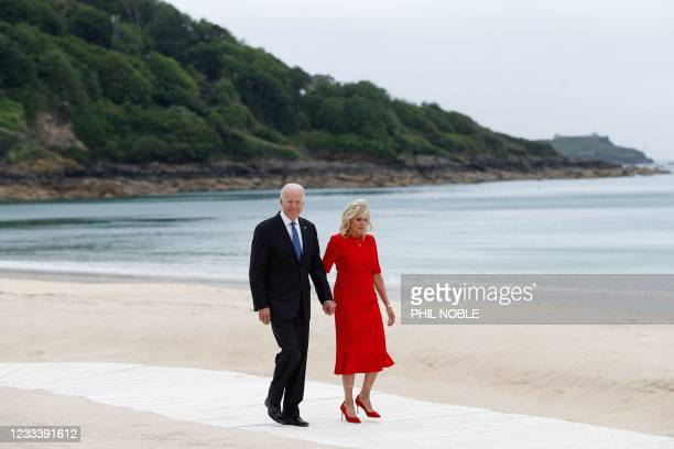 President Joe Biden and US First Lady Jill Biden walk along the path by the beach during the G7 summit in Carbis Bay, Cornwall, south-west England on...