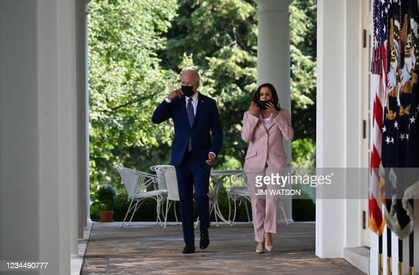 President Joe Biden and US Vice President Kamala Harris remove their masks as they arrive in the Rose Garden of the White House in Washington, DC,...