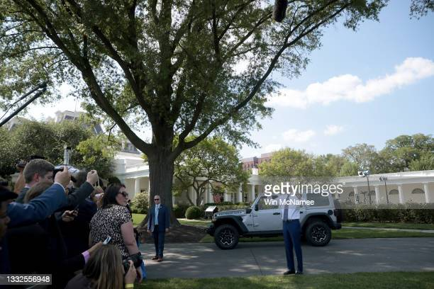 President Joe Biden answers questions from reporters after driving a Jeep Wrangler Rubicon Xe around the White House driveway following remarks...