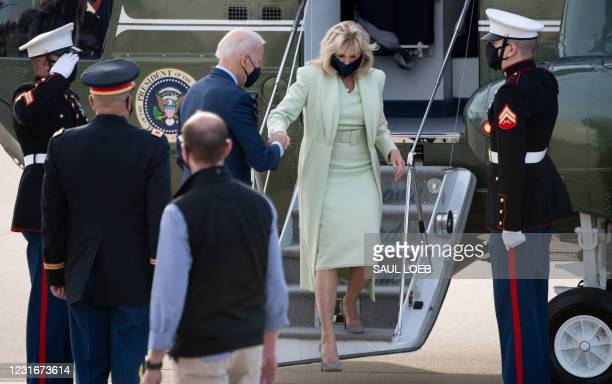 President Joe Biden assists First Lady Jill Biden as they disembark from Marine One after arriving at Delaware Air National Guard Base in Wilmington,...