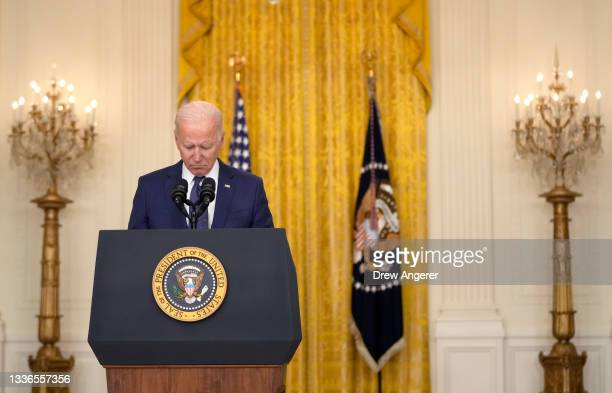 President Joe Biden bows his head in a moment of silence as he speaks about the situation in Kabul, Afghanistan from the East Room of the White House...