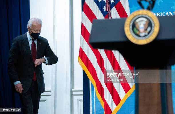 President Joe Biden checks his watch as he arrives to speak about the American Rescue Plan and the Paycheck Protection Program for small businesses...