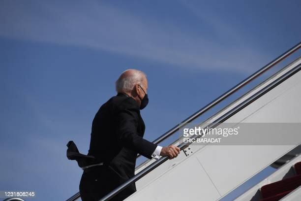 President Joe Biden continues up the steps after tripping while boarding Air Force One at Joint Base Andrews in Maryland on March 19, 2021. -...