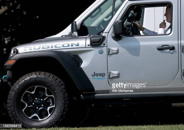 President Joe Biden drives a Jeep Wrangler Rubicon Xe around the White House driveway following remarks during an event on the South Lawn of the...