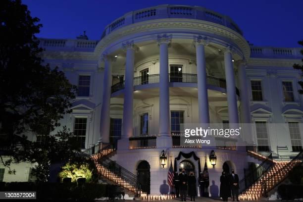 President Joe Biden, first lady Jill Biden, Vice President Kamala Harris and husband Doug Emhoff participate in a moment of silence at sundown in the...