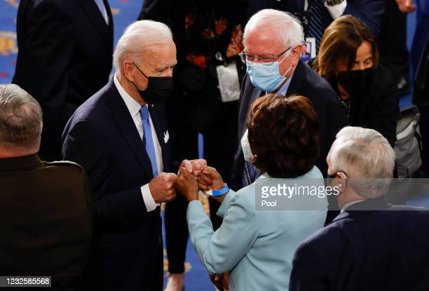 President Joe Biden fist bumps U.S. Rep. Maxine Waters as Senator Bernie Sanders looks on after Biden concluded his first address to a joint session...