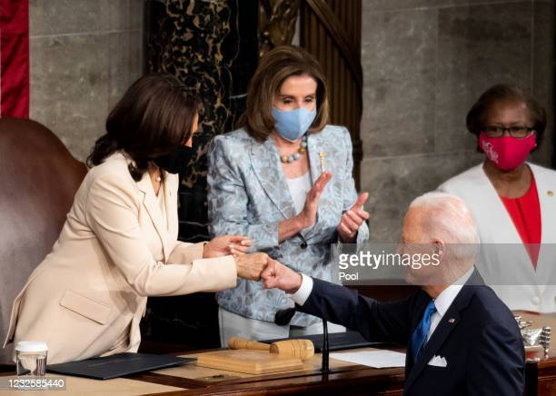 President Joe Biden fist bumps Vice President Kamala Harris as Speaker of the House Nancy Pelosi, D-Calif., claps at the end of his address to the...