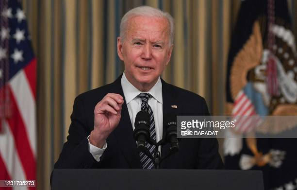 President Joe Biden gestures during remarks on the implementation of the American Rescue Plan in the State Dining room of the White House in...