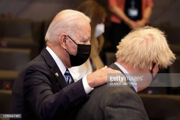 President Joe Biden greets Britain's Prime Minister Boris Johnson during a plenary session of a NATO summit at the North Atlantic Treaty Organization...