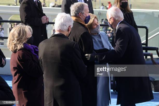 President Joe Biden greets former U.S President George W. Bush and his wife Laura Bush, and former U.S. President Bill Clinton and his wife, former...
