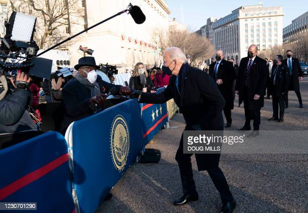 President Joe Biden greets NBC anchor Al Roker as he and and First Lady Dr. Jill Biden walk along Pennsylvania Avenue in front of the White House...