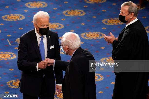 President Joe Biden greets Sen. Bernie Sanders as Supreme Court Chief Justice John Roberts looks on before a joint session of Congress in the House...