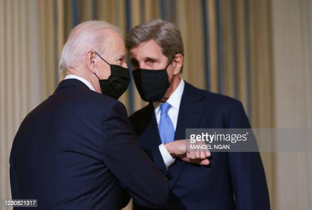 President Joe Biden greets Special Presidential Envoy for Climate John Kerry as he arrives to speak on climate change before signing executive orders...