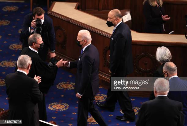 President Joe Biden greets Supreme Court Justice John Roberts with a fist bump before addressing a joint session of congress in the House chamber of...
