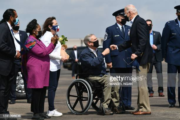 President Joe Biden greets Texas Governor Greg Abbott and his wife Cecilia Abbott at Ellington Field Joint Reserve Base in Houston, Texas on February...