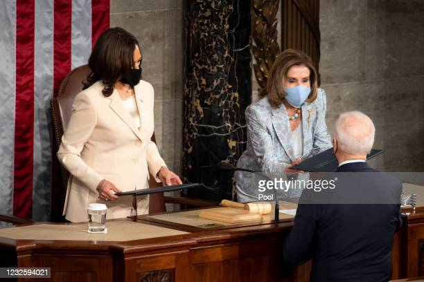 President Joe Biden hands a copy of his speech to Speaker of the House Nancy Pelosi, D-Calif., after delivering his address to the joint session of...