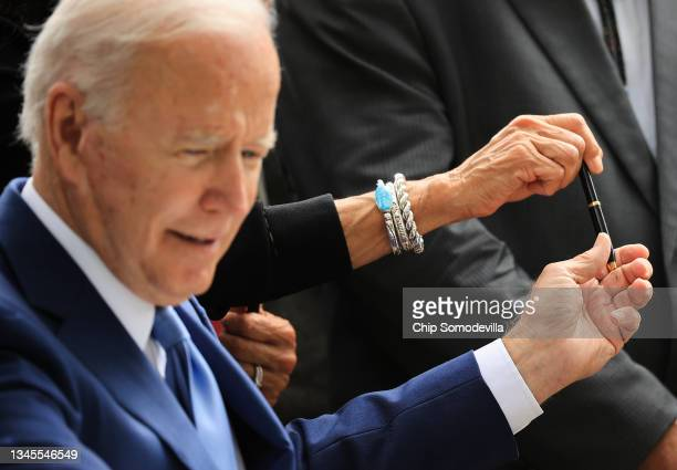 President Joe Biden hands a pen to Secretary of the Interior Deb Haaland after signing an executive order to expand the areas of three national...