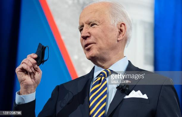 President Joe Biden holds a face mask as he participates in a CNN town hall at the Pabst Theater in Milwaukee, Wisconsin, February 16, 2021.