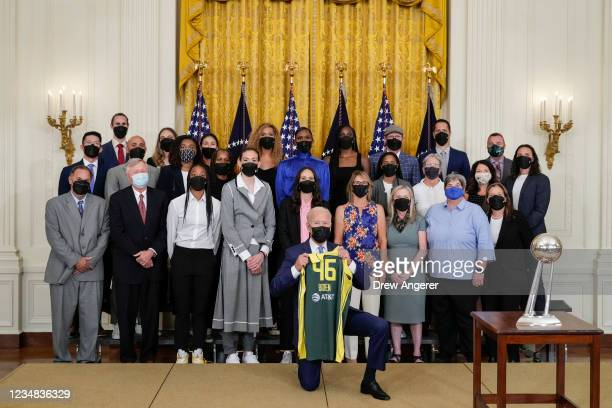 President Joe Biden holds a jersey as he poses for a photo with the 2020 WNBA champions Seattle Storm in the East Room of the White House on August...