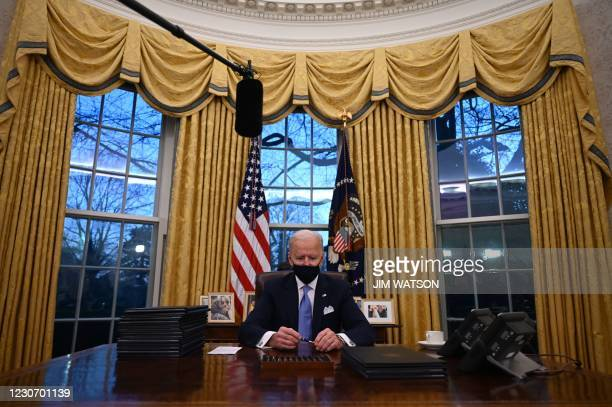 President Joe Biden holds a pen as he prepares to sign a series of orders in the Oval Office of the White House in Washington, DC, after being sworn...